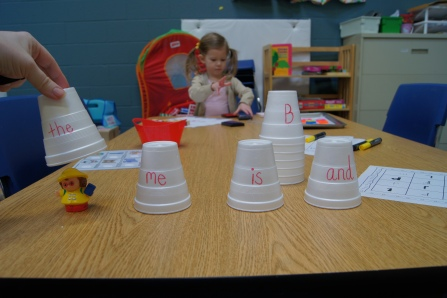 I put different sight words on cups and found a person that most looked like a letter carrier.  The parent hid the toy under a cup and the kids had to guess which one it was under.    I also had some cups that had letters on them, in case a parent felt that there child wasn't ready for sight words quite yet.
