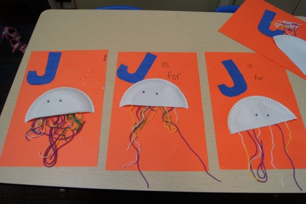 "For our craft, we made a ""J is for Jellyfish"" poster.  I had a non-fiction book with pictures of jellyfish for the kids to reference.  I had one ""J"", a half of a paper plate, a piece of large paper, glue, a marker, and tons of strings available for each child."
