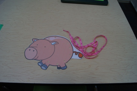 I printed and laminated a lacing pig card and had a shoelace to weave through the holes.  I found the pig (and there are much more options) here.