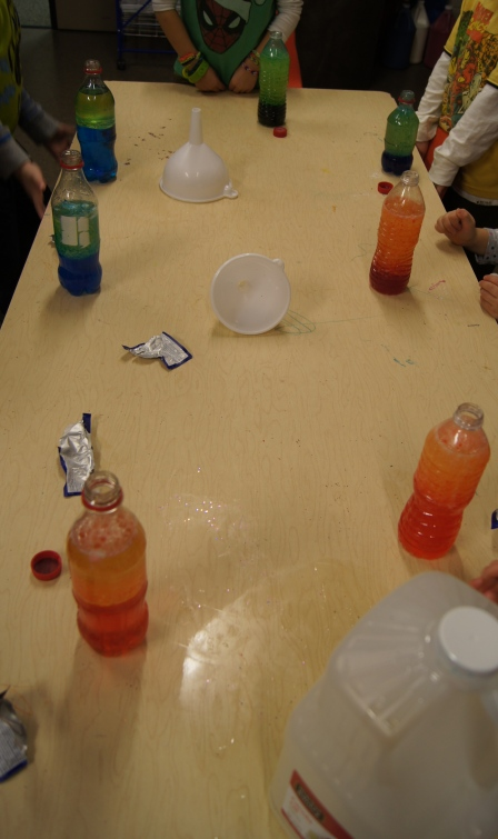 After our observation of the six-layer density cup, the children made their own two-layer density jar.  We used recycled clear plastic containers, funnels, food coloring, water, and oil.  The kids chose the colors that they wanted, poured the oil and water and watched them separate.  We talked about why they separated and which was more dense.