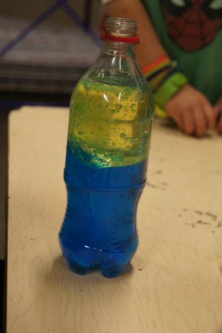 We added alka-seltzer to the bottles and watched as the more dense water rose up only to be separated again.  The kids love this!!  I wanted the kids to take this home, but I didn't want any of the bottles to open in their backpacks or anyone to try to take a drink.  Therefore, when we were finished with the experiment, I hot-glue gunned the tops on each bottle.  I made sure that all of the Oxygen had escaped each bottle before I put the top on it.
